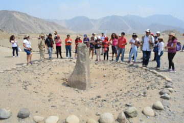 Tour Group looking at Sundial in Caral, Peru
